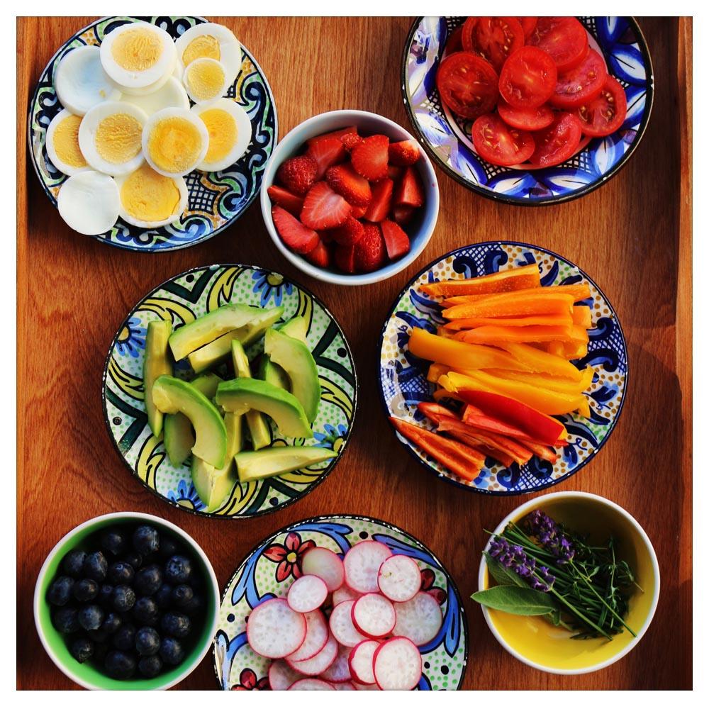 Acht Schüsseln, die mit Eiern, Erdbeeren, Tomaten, Avocados, Karotten, Heidelbeeren, Radieschen und Lavendel gefüllt sind.